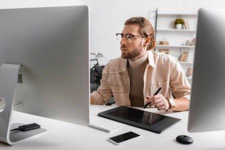 Photo pour Beau artiste 3d en utilisant des tablettes graphiques et des ordinateurs à la table dans le bureau - image libre de droit
