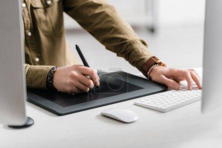 Photo pour Vue recadrée du concepteur travaillant avec une tablette graphique et un clavier d'ordinateur sur la table - image libre de droit