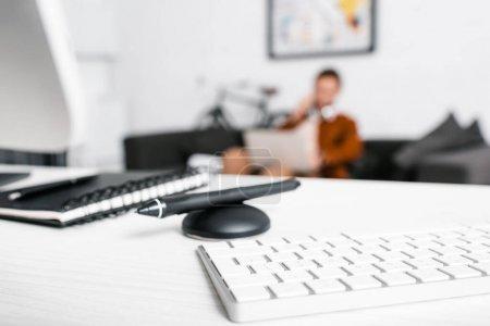 Photo pour Mise au point sélective du clavier d'ordinateur, bloc-notes et stylet de tablette graphique sur table et concepteur avec ordinateur portable sur divan au bureau - image libre de droit