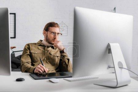 Photo pour Concentration sélective de l'artiste 3D en utilisant une tablette graphique et un ordinateur tout en travaillant avec le projet dans le bureau - image libre de droit
