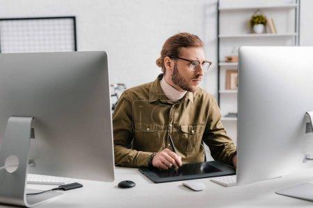 Photo pour Beau concepteur 3D travaillant avec des ordinateurs et tablette graphique sur la table dans le bureau - image libre de droit