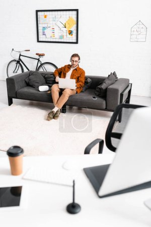 Photo for Selective focus of 3d artist in headphones using laptop near smartphone and virtual reality headset on couch in office - Royalty Free Image
