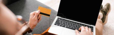 Photo pour Concentration sélective du concepteur numérique à l'aide d'un ordinateur portable et tenant la carte de crédit sur le canapé, prise de vue panoramique - image libre de droit