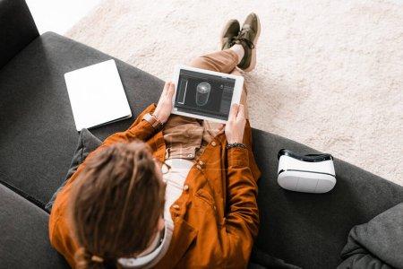 Foto de Vista general de la tableta de diseño digital con un proyecto de diseño de 3d cerca de laptop y auriculares vr en sofá. - Imagen libre de derechos