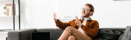 Panoramic shot of smiling 3d artist showing peace sign while having video call on digital tablet near laptop on couch