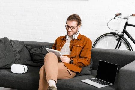 Photo pour Souriant artiste numérique en utilisant tablette près vr casque et ordinateur portable sur le canapé - image libre de droit