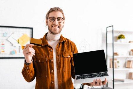 Photo pour Artiste 3d souriant à la caméra et tenant la carte de crédit et ordinateur portable dans le bureau - image libre de droit