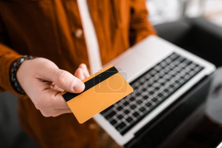 Selective focus of 3d artist holding credit card and laptop with blank screen