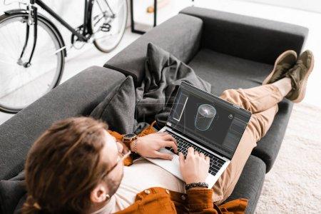 Photo pour Vue aérienne du concepteur numérique travaillant avec un projet de conception 3D sur un ordinateur portable sur un canapé dans un bureau - image libre de droit