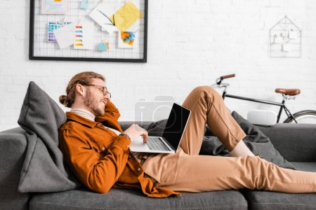 Photo for Side view of smiling 3d artist using laptop near vr headset on couch in office - Royalty Free Image
