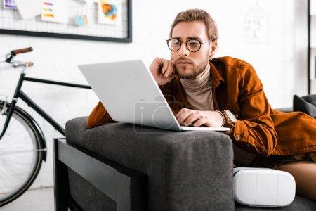 Photo pour Beau concepteur numérique travaillant avec ordinateur portable près vr casque sur le canapé - image libre de droit