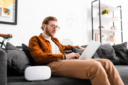 Photo for Handsome digital designer using laptop near virtual reality headset on couch in office - Royalty Free Image