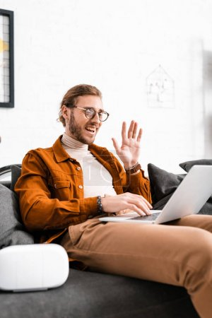 Photo for Selective focus of cheerful 3d designer waving hand while having video call on laptop near vr headset on couch - Royalty Free Image