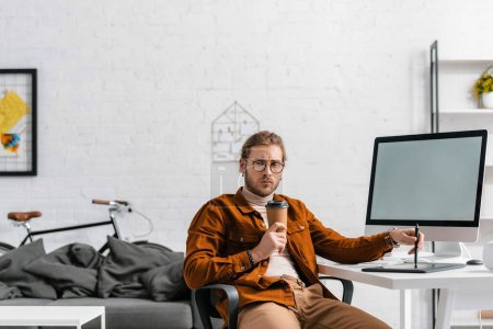 Photo for Pensive digital designer with paper cup holding stylus near graphics tablet and computer on table - Royalty Free Image