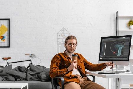 Photo pour Concepteur numérique réfléchi tenant tasse en papier et stylet près de la tablette graphique et projet de conception 3D sur écran d'ordinateur sur la table - image libre de droit