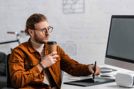 Photo for Handsome 3d visualizer holding coffee to go and using graphics tablet near computer and vr headset on table - Royalty Free Image