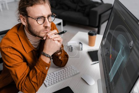 Photo for High angle view of thoughtful digital designer holding stylus near project of 3d design on computer monitor on table - Royalty Free Image