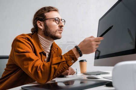 Photo for Selective focus of 3d artist pointing with stylus on computer monitor at table in office - Royalty Free Image