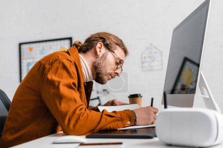 Photo pour Vue latérale du bel artiste 3d écrivant sur ordinateur portable près de gadgets sur la table au bureau - image libre de droit
