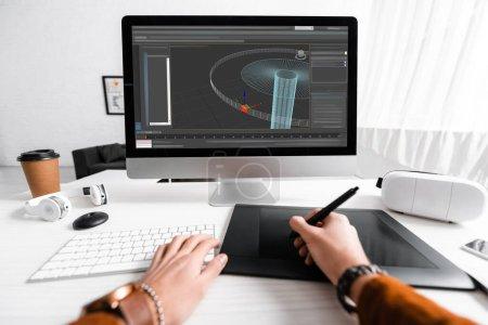 Photo pour Vue recadrée du concepteur numérique en utilisant la tablette graphique et le clavier d'ordinateur tout en travaillant sur le projet de conception 3D à la table - image libre de droit