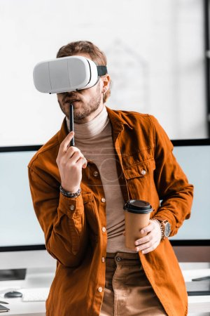 Photo for Digital designer in vr headset holding stylus of graphics tablet and coffee to go near computer monitors in office - Royalty Free Image
