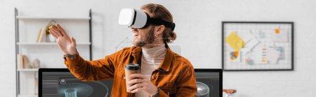 Foto de Foto panorámica de un alegre artista de 3d en auriculares vr que sostiene café para acercarse al proyecto de diseño de 3d en monitores de computadoras en la oficina. - Imagen libre de derechos