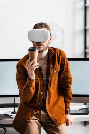 Photo for Digital designer in virtual reality headset holding paper cup near computer monitors on table - Royalty Free Image