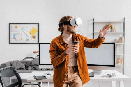 Smiling 3d artist using virtual reality headset and holding coffee to go in office