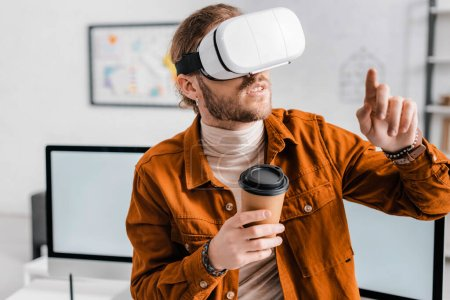 Photo for 3d artist in virtual reality headset holding coffee to go and pointing with finger in office - Royalty Free Image