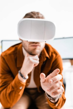 Selective focus of 3d artist in vr headset gesturing on white background