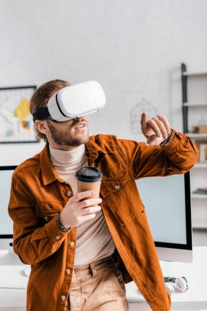Photo for Digital designer pointing with finger while using virtual reality headset and holding paper cup in office - Royalty Free Image