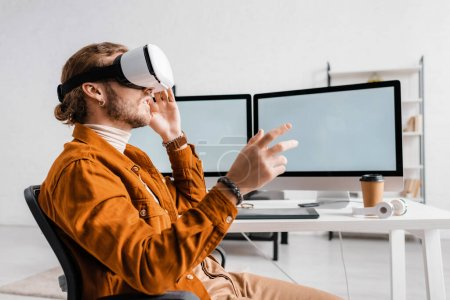 Photo for Side view of 3d artist gesturing while using vr headset near digital devices on table - Royalty Free Image