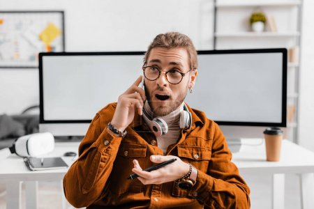 Photo for Shocked 3d artist talking on smartphone and holding stylus of graphics tablet in office - Royalty Free Image