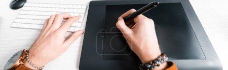 Photo pour Vue recadrée du concepteur numérique travaillant avec tablette graphique et clavier d'ordinateur à la table, prise de vue panoramique - image libre de droit