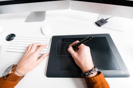 Photo pour Vue recadrée du concepteur numérique travaillant avec tablette graphique et clavier d'ordinateur à la table - image libre de droit