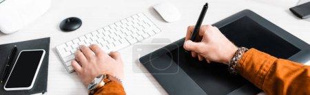 Photo pour Vue agrandie d'un artiste 3D utilisant une tablette graphique et un clavier d'ordinateur près d'un smartphone et d'un casque d'écoute vr sur une table, prise de vue panoramique - image libre de droit
