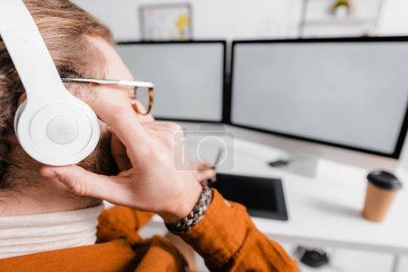 Photo pour Concentration sélective de l'artiste 3D écoutant de la musique tout en rendant le projet sur les ordinateurs dans le bureau - image libre de droit