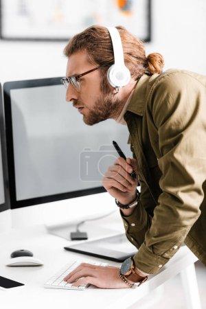 Photo pour Vue latérale du beau concepteur numérique dans les écouteurs à l'aide d'un ordinateur et tenant le stylet de la tablette graphique à la table dans le bureau - image libre de droit
