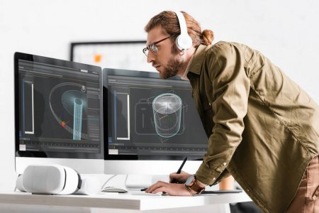 Photo pour Side view of 3d artist in headphones working on project of 3d design near vr headset on table - image libre de droit