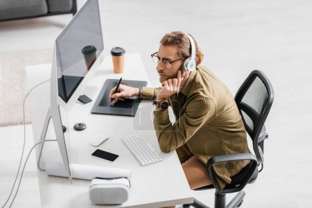 Photo pour Vue latérale de l'artiste 3D dans les écouteurs écoutant de la musique tout en travaillant avec des tablettes graphiques et des ordinateurs à la table - image libre de droit