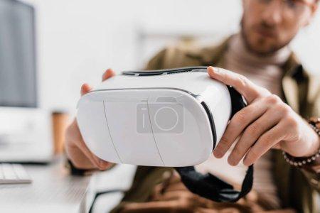 Photo pour Focus sélectif de l'artiste 3d tenant casque de réalité virtuelle à table - image libre de droit