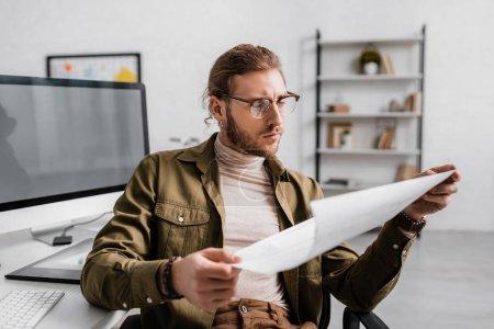 Photo pour Focus sélectif de l'artiste 3D regardant le plan tout en travaillant à la table au bureau - image libre de droit