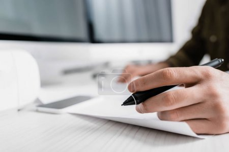 Photo for Cropped view of 3d artist holding stylus of graphics tablet near paper on table - Royalty Free Image