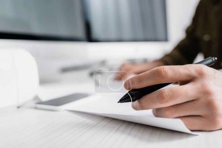 Photo pour Vue recadrée de l'artiste 3d tenant stylet de tablette graphique près du papier sur la table - image libre de droit