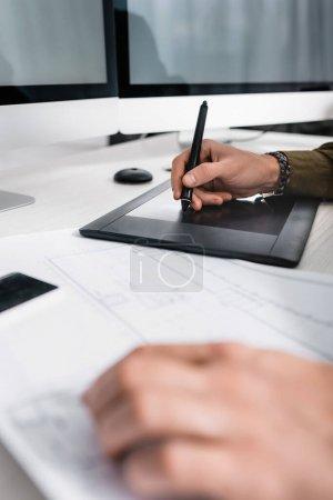 Photo pour Mise au point sélective de l'artiste 3D en utilisant une tablette graphique près du plan tout en travaillant à la table - image libre de droit
