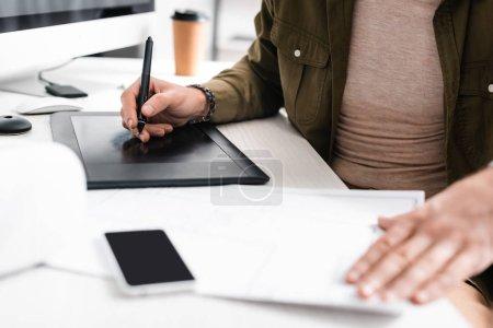 Photo pour Concentration sélective du concepteur numérique travaillant avec une tablette graphique, un ordinateur et un plan sur la table - image libre de droit
