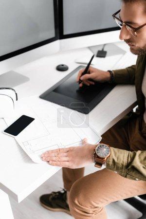 Foto de Diseño digital práctico usando blueprint mientras se trabaja con gráficos comprimidos y computadoras cerca de auriculares vr en la mesa. - Imagen libre de derechos