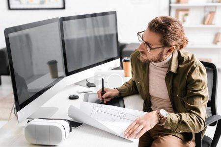 Photo pour Artiste 3D utilisant le plan, les tablettes graphiques et les ordinateurs à la table dans le bureau - image libre de droit