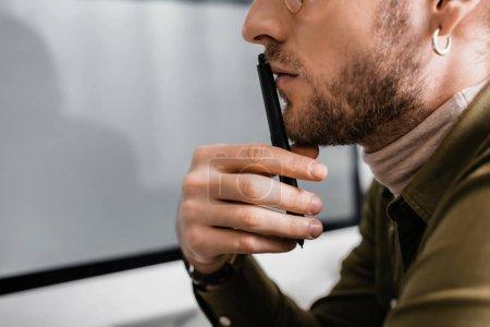 Photo pour Vue recadrée de l'artiste 3d tenant stylet de tablette graphique près de l'écran d'ordinateur sur fond gris - image libre de droit