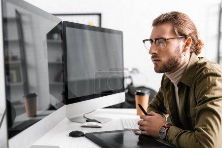 Photo for Side view of handsome 3d artist holding stylus near graphics tablet and looking at computer monitors with blank screen on table - Royalty Free Image